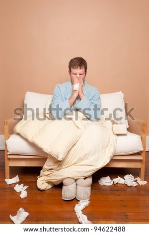 A sick man on the couch blowing his nose