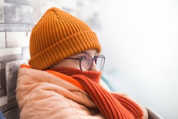 A sick teenager girl is sitting on a sofa wrapped in a blanket and wearing a hat with a scarf. At home.