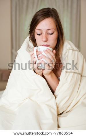 A sick young lady in bed, sitting with a blanket over her shoulders and a cup of hot beverage.