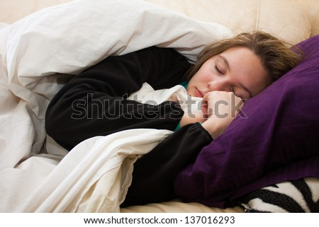 A sick young woman takes a nap on the couch, cuddled up with a blanket and