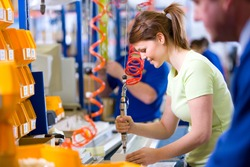 A side profile medium shot of a happy young female worker in casuals operating machinery on a production line in a factory.