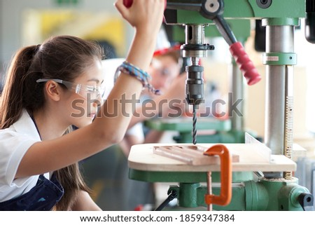 A side profile shot of a young girl using a drill machine in a vocational school. Stock photo ©