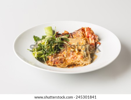 A side view of a dinner or lunch plate with the Italian pasta dish, lasagne and a small vegetable salad on the side as garnish.