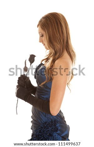 a side view of a teen in her blue prom dress holding onto her black rose.