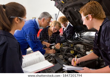 A side view of a trainer closely watching his student repair a car in a vocational school of automotive trade