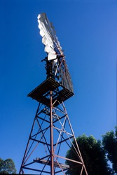 A side view of a windmill which draws water up from a bore silhouetted against a blue sky in vertical format.