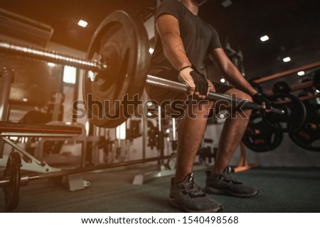 A side view of a young bodybuilder exercising in the gym, ready to lift weights, lift weights, work out all leg muscles and parts of the body.