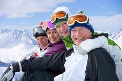 A side view portrait of a smiling couples in ski outfit sitting in a row on a snowy mountain