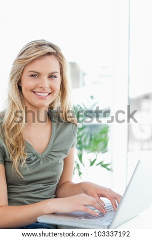 A side view, woman using her laptop on the couch as she smiles and looks forward.