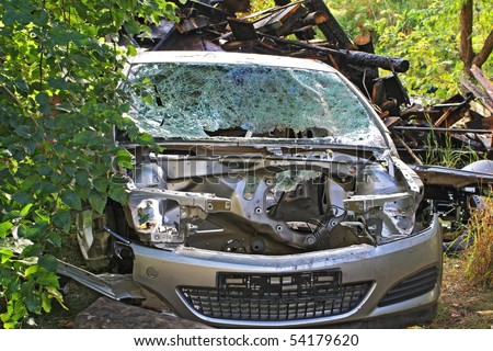 A sight of a car broken in a car crash with scorched ruins on the background