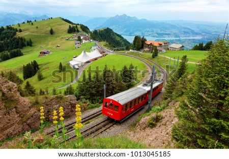 A sightseeing train traveling on the cogwheel railway through green grassy meadows on Mt. Rigi, with rugged Pilatus peaks among majestic mountains in background on a cloudy summer day in Switzerland Stock fotó ©
