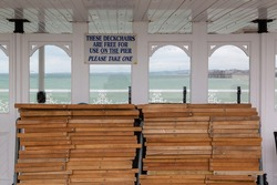 A sign above deck chairs on a pier reading that deckchairs are free to use on the pier at the British seaside