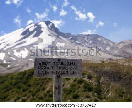 A sign at the trailhead near Windy Ridge that shows the open crater of the Mt. St. Helens volcano in the background.