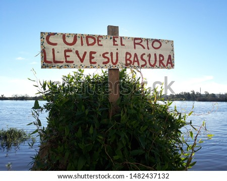 a sign by the river, attached to a tree, written: take care of the river, take your trash Foto stock ©