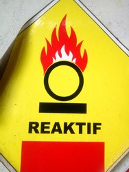 a sign dangerous reactive with symbol burn