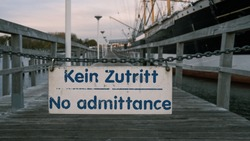 a sign hanging on a chain says: no admittance