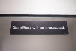 A sign in a changing room of a retail store reads