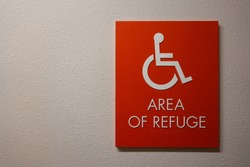 A sign in a hallway in an apartment complex that says Area of Refuge with a wheelchair symbol on it that is an emergency gathering area for disabled people.