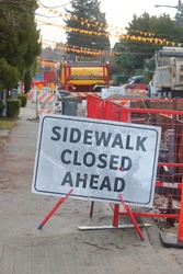 A sign informs pedestrians that the sidewalk is closed/Sidewalk Closed Ahead Signage/Street construction has closed the sidewalk for pedestrians.