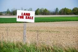 A sign is in front of the land. Land for sale.