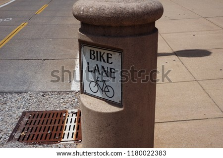 A sign of bike path with bicycle illustration for safe road sharing.  Healthy and good for environment way of travel when street has space to share with cars.  Exercise fun                             #1180022383