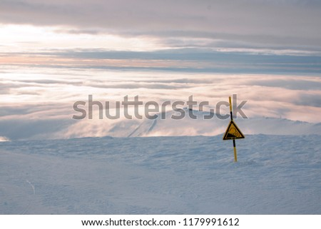 A sign of danger or steep descent on the track in a ski resort in winter, a landscape with snow and clouds on the horizon