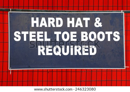 A sign on a construction site requires a hard hat and steel toe boots/Hard Hat and Boots Required Sign/A sign on a construction site requires a hard hat and steel toe boots.