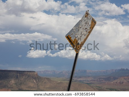 A sign on a rural desert road has been so badly shot up that it's no readable.  Horizontal image.