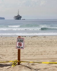 A sign posted on the beach warns that the water is closed due to an oil spill. An offshore drilling platform is visible in the distance.