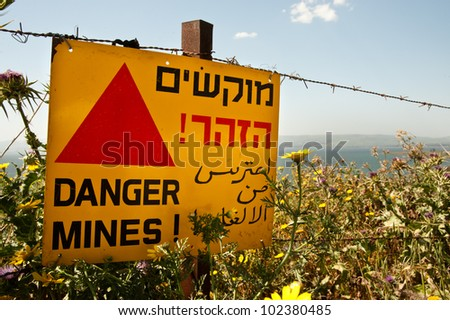 "A sign reading ""Danger Mines!"" hangs from a barbed wire fence in the Golan Heights. Effectively annexed by Israel in 1981, the Golan is still considered occupied territory under international law."