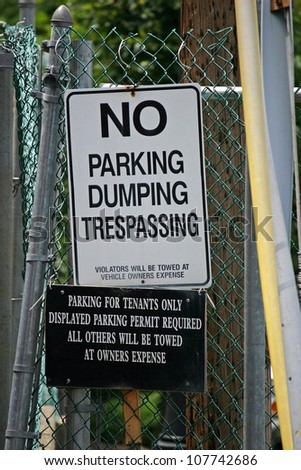 A sign reading No Parking, Dumping, Trespassing against a green fence