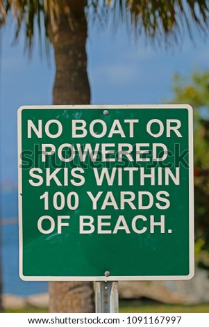 A Sign Saying No Boat or Powered Skis Within 100 Yards of Beach #1091167997