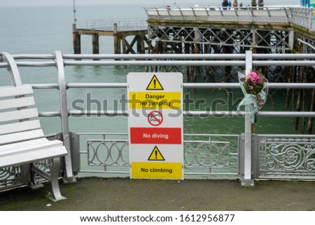 A sign stating no swimming or diving from a pier with a bunch of flowers left next to it after a fatal accident