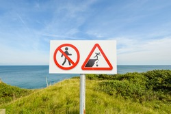 A sign warning hikers and visitors to be cautious walking and avoid crumbling rocks on the cliff at the WWII battle site of Pointe du Hoc, in Normandy, France.