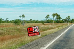 A sign warning of roadworks ahead and for motorists to reduce speed to 60 kilometers per hour on a country highway