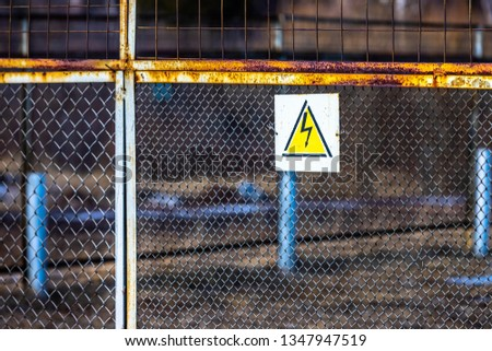 A sign warning of the dangers of high electrical voltage hangs on the mesh fence that surrounds the power line substation. #1347947519