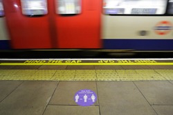 A sign warning people to maintain social distancing due to Coronavirus, COVID-19 pandemic, is seen in a metro station in central London, United Kingdom.