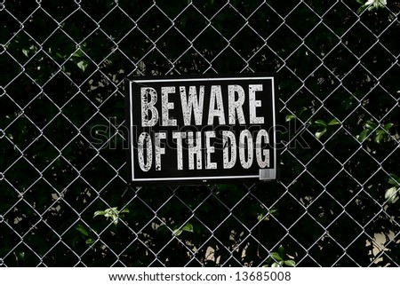 A sign warning the reader to beware of the dog, on a chain link fence backdrop.