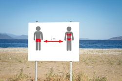 A sign warns beach goers to socially distance due to the COVID-19 global pandemic.