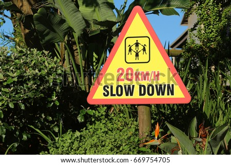 A sign warns drivers to slow down to 20 km/h because of children playing.