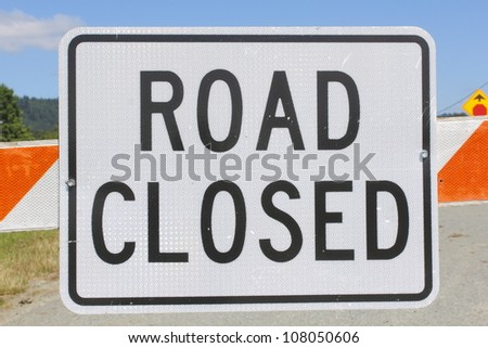 A sign warns that the road up ahead is closed/Road Closed Sign/A metal sign in bold capitol letters warns that the road is closed up ahead.