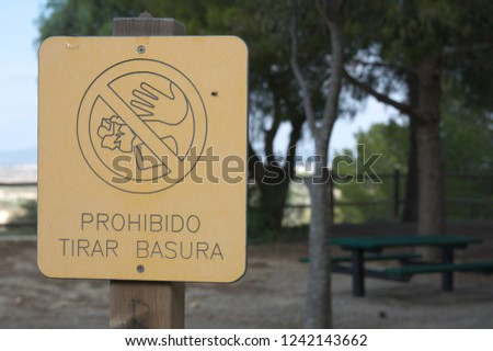 """A sign where it says in Spanish: """"Prohibido tras basura"""", that is to say, It is forbidden to throw garbage in a recreational area destined to spend pleasant summer days. #1242143662"""