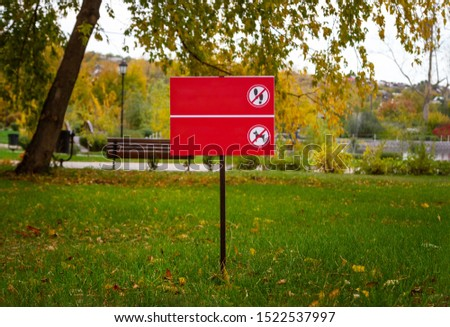 Photo of A sign with a picture prohibiting dog walking on a green lawn. The ban on walking on the green lawn.Mockup free. Horizontal.