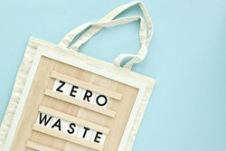 A sign with the inscription Zero waste on a fabric bag on a light blue background. Flat layout, top view, a place to copy.