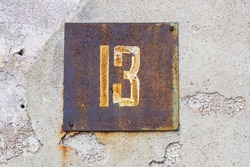a sign with the number thirteen on the wall of the house. unfortunate number. High quality photo