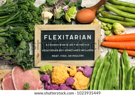 a signboard with the text flexitarian and its definition on a pile of some different raw vegetables, such as cauliflower of different colors, broccolini, beans, and some eggs and slices of meat