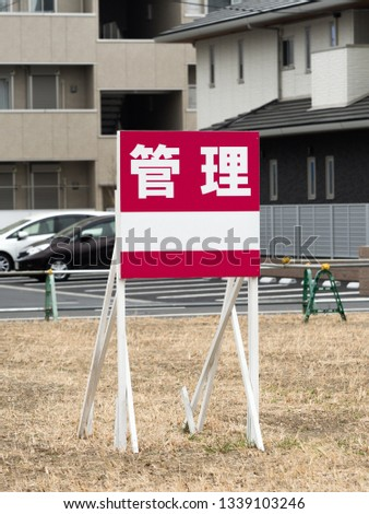 """A signboard written in Japanese with the word """"management"""" installed in a vacant land #1339103246"""
