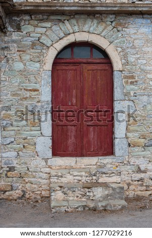 A significant red door of a stone building #1277029216