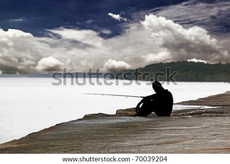 A silhouette of a angler fishing on a concrete sea embankment with a dramatic sky as a backdrop.