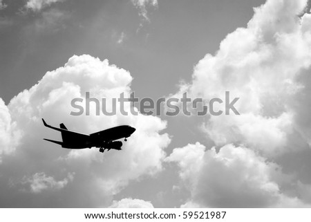 A silhouette of a commercial passenger plane over partly cloudy sky in its descent to land.